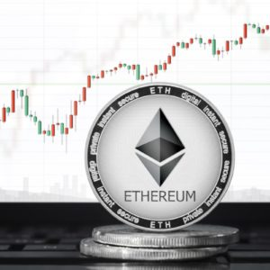 Picture of an ethereum coin standing on two other coins with a candlestick price chart behind it