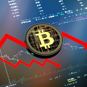 Bitcoin with two red downwards pointing arrows behind it on top of a crypto chart