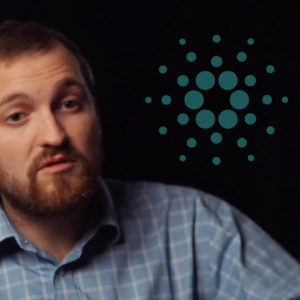 Picture of Cardano co-founder Charles Hoskinson with a Cardano logo behind him on a black background