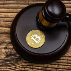 Picture of a bitcoin sitting on top a mallet, with a gavel resting next to it