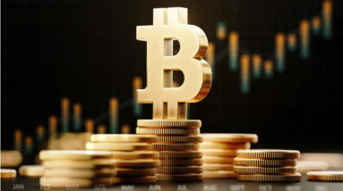 Picture of a bitcoin symbol standing on top of stacked gold coins, with a red candlestick chart behind it