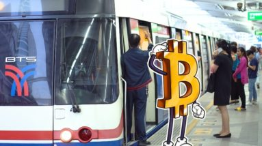 Picture of a bitcoin saluting with people getting on a train behind it
