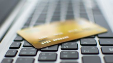 Picture of a gold debit card on a computer keyboard, depicting COTI debit cards